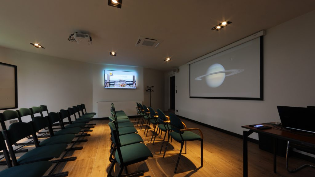 """De """"Saturnus"""" zaal op het tuinverdiep van Hostellerie Kemmelberg ****  kan in diverse opstellingen worden opgezet. Hier zien we een mogelijke  """"theater""""-opstelling (90° gedraaid)."""