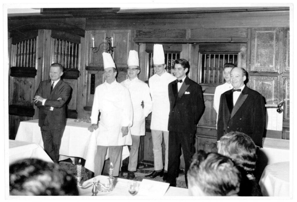 Begin van de jaren zestig: de volledige zaalequipe van Hostellerie Kemmelberg. We herkennen links Directeur Walter Geissler (= de eerste zaakvoerder). Naast hem staat chef kok Raymond Doulet. De middelste kok is Antoon Bommarez (die later de vzw Westvlaamse Grootkeukenkoks oprichtte). [Foto afkomstig uit het archief van Antoon Bommarez, kok in HMK 1960-1966]